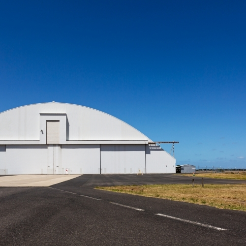 Airplane hangar with rounded top and clear blue sky