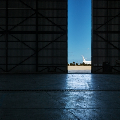 Inside an airport hangar looking out to a plane on the runway through a narrow opening
