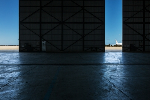 Inside an airport hangar looking out to the runway