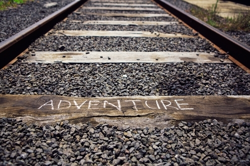 Close up of train track with the word Adventure written on a sleeper