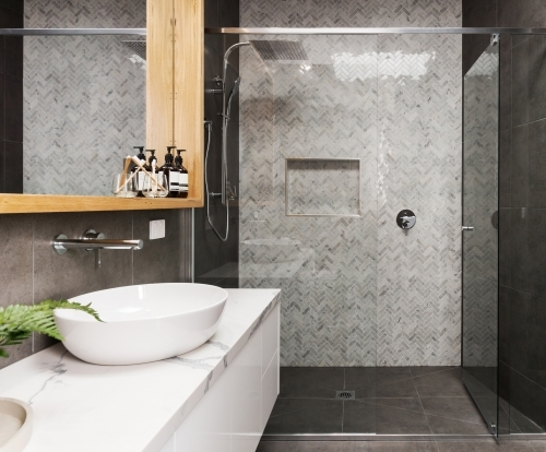 Marble mosaic herringbone tiled shower feature in a contemporary ensuite bathroom