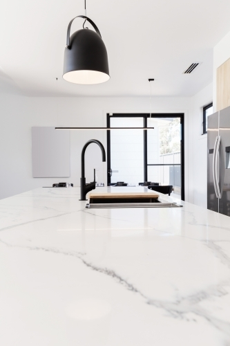 Carrara marble benchtop with black gooseneck kitchen tap and black pendant