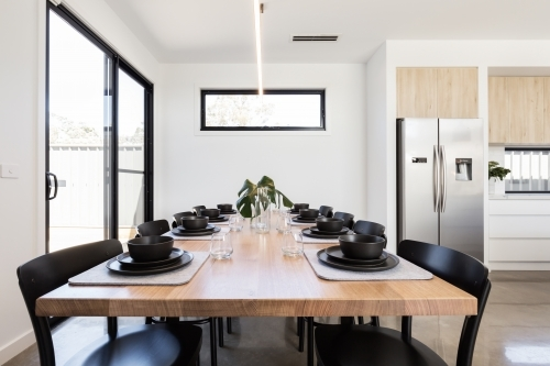 Gorgeous dinner setting of black crockery on an oak table in a modern home