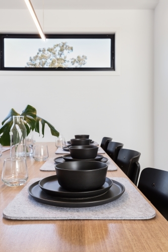 Table setting details of charcoal crockery and felt grey placemats