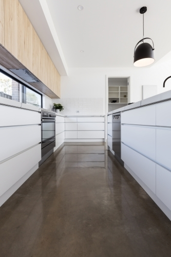 Long galley style kitchen with polished concrete floor