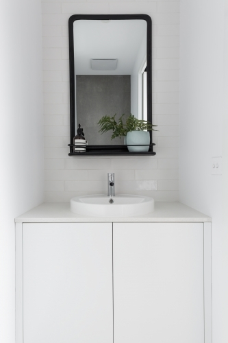 Monochrome powder room vanity black mirror and white tiling