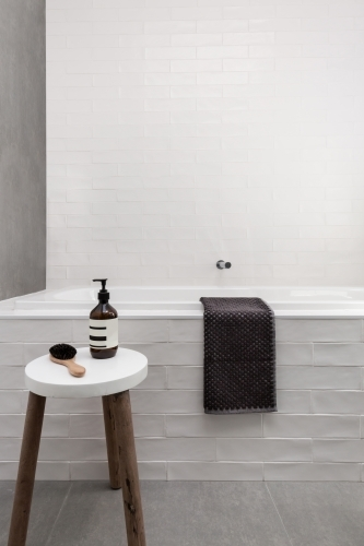 White bath hob and stool with soap day spa bathroom