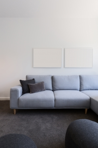 Vertical image of pastel blue sofa with blank artwork above