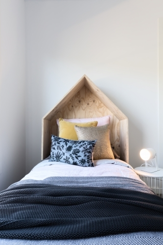 Cute wooden tent style wooden bedhead in a styled children's bedroom