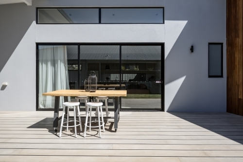 Sunny outdoor entertaining deck with triple glass sliding doors