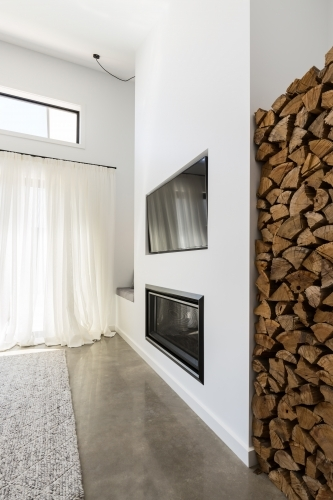 Stacked firewood alcove next to living room tv and fireplace