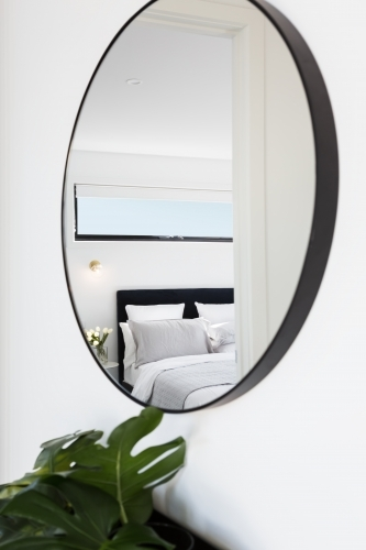View of a luxury bedroom reflected in a hallway mirror