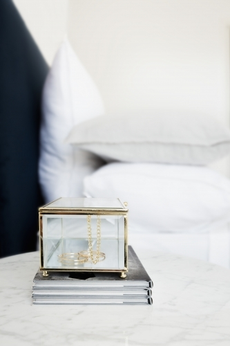 Gold and glass jewellery box and books on bedside table