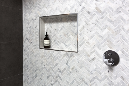 Show shelf detail in wall of herringbone marble tiles