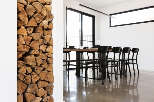 Wood stack feature in lounge with dining table in background