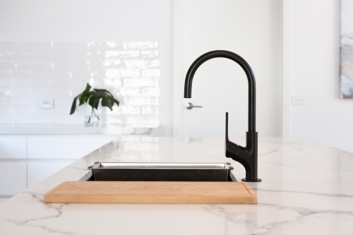 Monochrome kitchen detail of black gooseneck tap