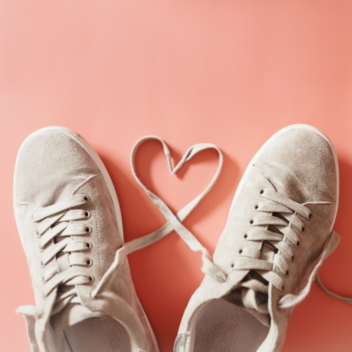 Pair of grey runners with laces making a heart shape