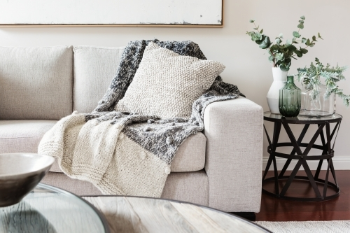 Textured layers interior styling of cushion sofa and throw in neutral colors