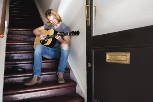 Young guy smiling playing guitar in a stairway