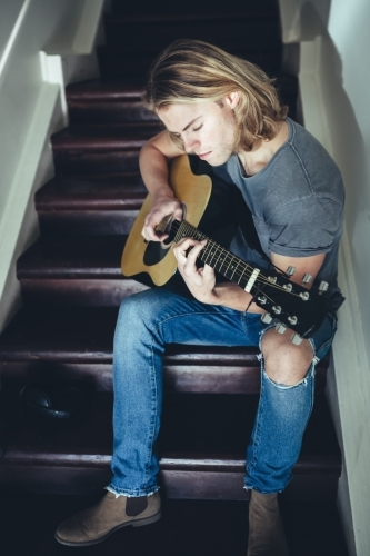 Young guy playing guitar alone with a serious facial expression