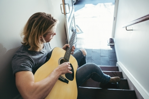 Blonde musician playing guitar in apartment stairs horizontal
