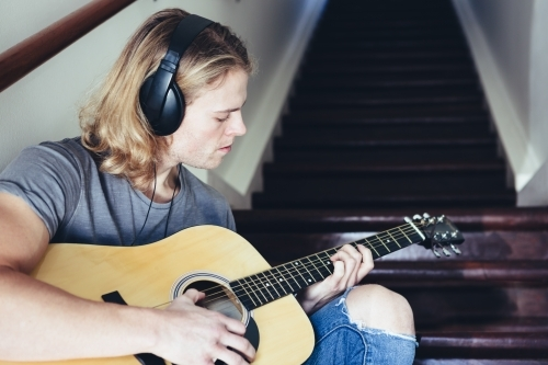 Musician playing guitar with headphones on