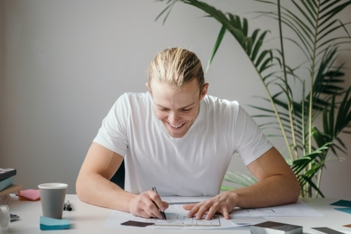 Happy designer working at a desk with indoor plant behind