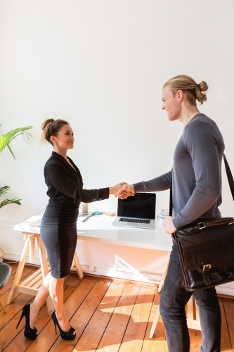 Two young business people greeting shaking hands