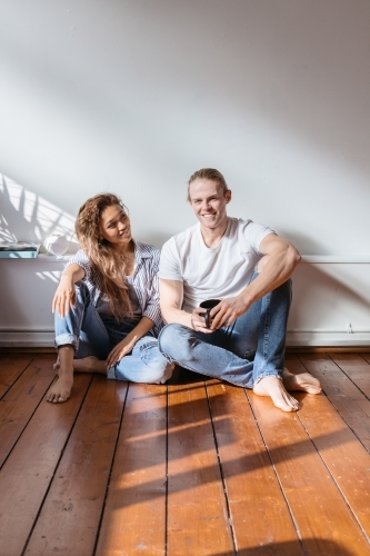 Happy couple sitting in their new apartment having coffee