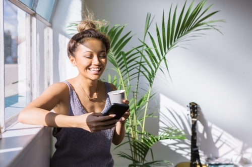 Young woman laughing while having coffee and looking at her phone