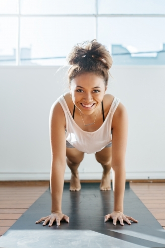 Fit girl performing a plank in a gym smiling at camera