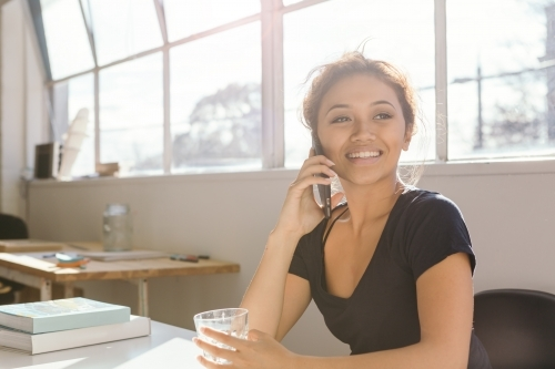 Successful young woman making a call in front of bright office windows