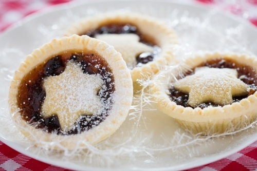 3 fruit mince pies on a white plate on top of a Christmas table cloth