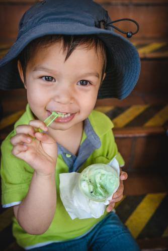 3 year old mixed race boy eating ice-cream on a warm summer day