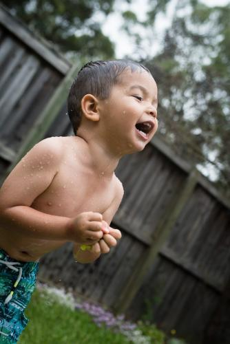 3 year old mixed race boy plays excitedly with water bombs in suburban backyard