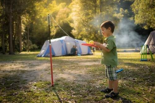 4 year old mixed race boy plays totem tennis on a camping trip