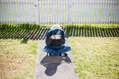 Woman sitting on path in front of white fence drinking coffee and holding smoke