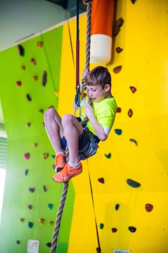 8 year old boy wearing climbing harness looking down whilst hanging on climbing rope
