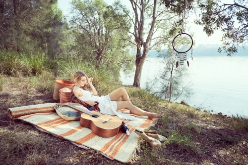 Girl having a picnic by the river with a guitar