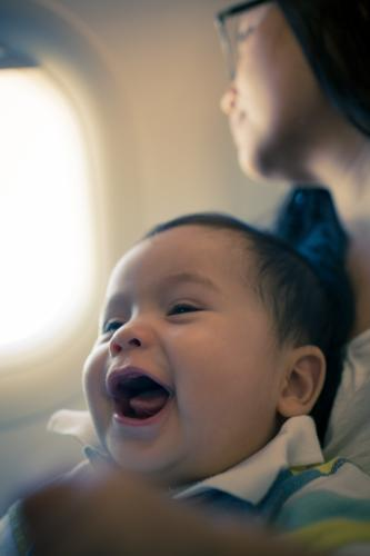 9 month old mixed race baby boy travels with his mother on a commercial aeroplane flight