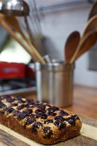 A baked cherry cake with kitchen utensils in the background