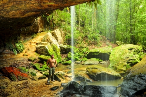 A bare-chested man in his mid forties admires the waterfall at Glow-Worm Nook Falls