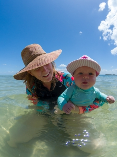 A blonde mum in her late thirties with baby playing at beach.
