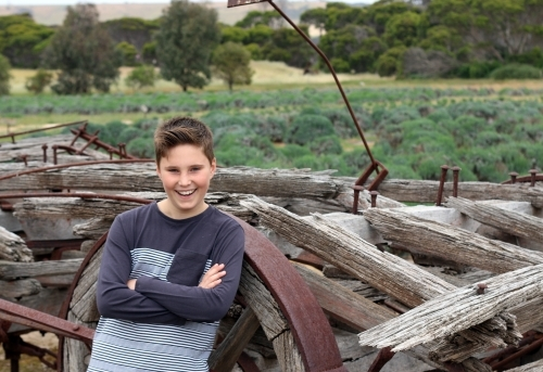 A boy smiling in front of a pile of wood and old rustic farm equipment