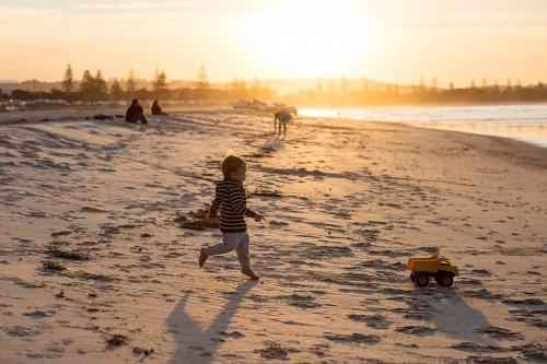 A Boy toddler, running after a toy truck on the beach at sunset