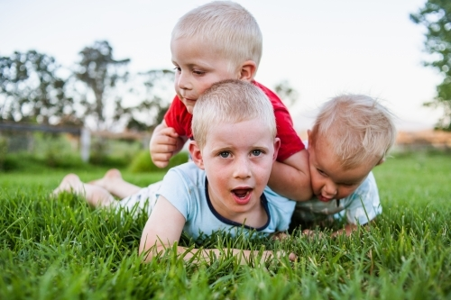 A close up of three brothers tackling each other in play on vibrant green grass.