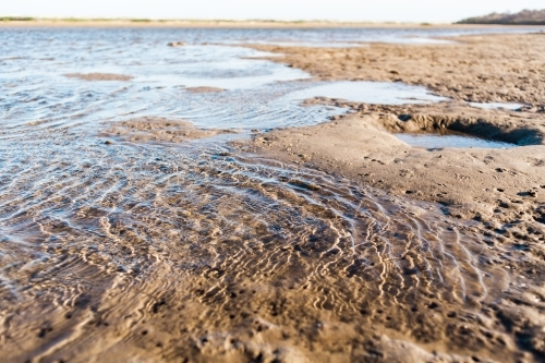 A close up of water ripples as the tide washes in against wet, soft sand of a lake at low tide.