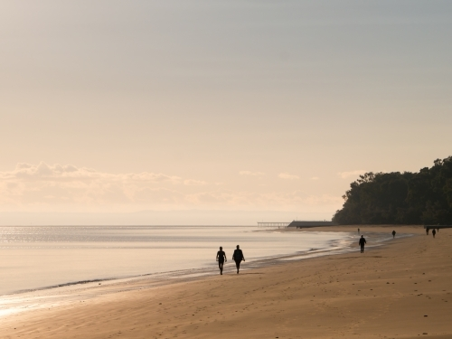 A couple walking along a quiet beach in the early morning