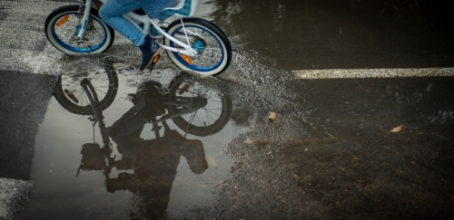 A cyclist riding around a puddle on the road.