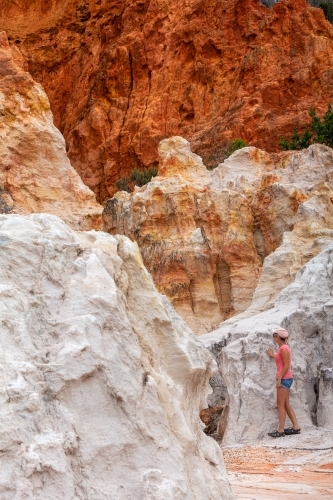 A female explores the Pinnacles a combination of white sands and red clay.